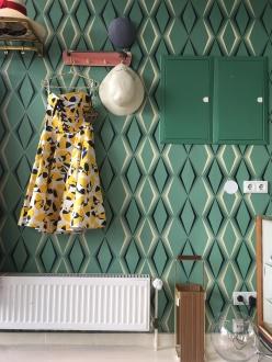 wie gut sich das gelbe Kleid vor der Vintage Tapete macht.