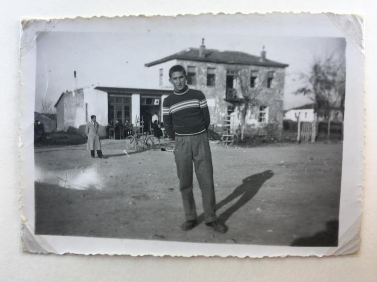 Georgios in seiner Heimat Griechenland. Hinter ihm sieht man das Haus und die Gaststätte der Familie.