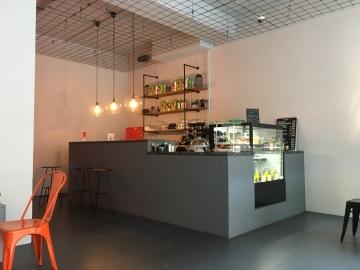 Die OFOF CAFÈBAR ist ein minimalistischen Rohbau mit hohen Decken und einem massiven Tresenbereich.
