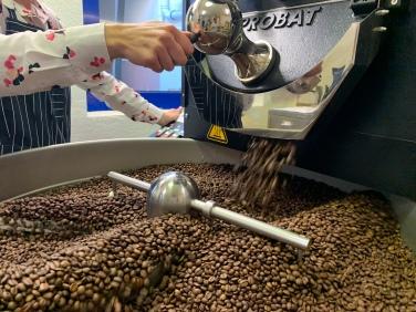 Wenn die Kaffeebohnen die richtige Röstung (Farbe) erreicht haben, öffnet Justyna die Klappe am Röstautomaten.